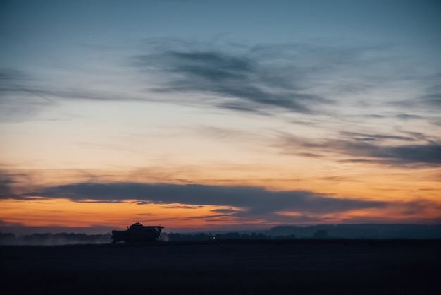 Silhouette of harvester machine to harvest wheat on sunset.