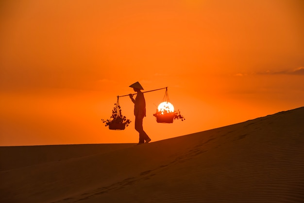 Silhouette of a hawker merchant traveling through the mui ne desert in vietnam