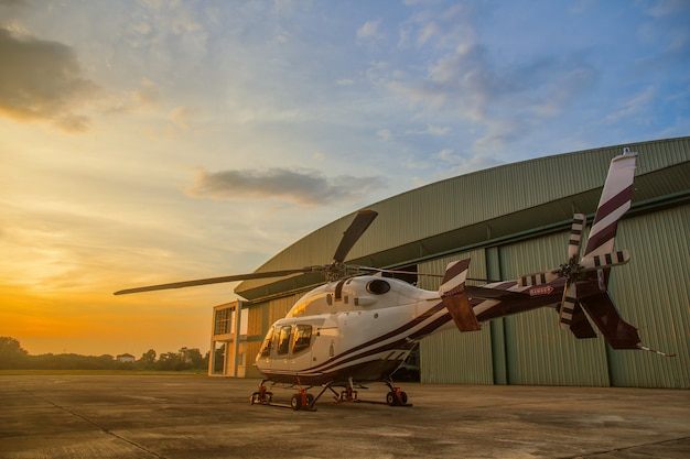 Silhouette of helicopter in the parking lot or runway with sunrise background