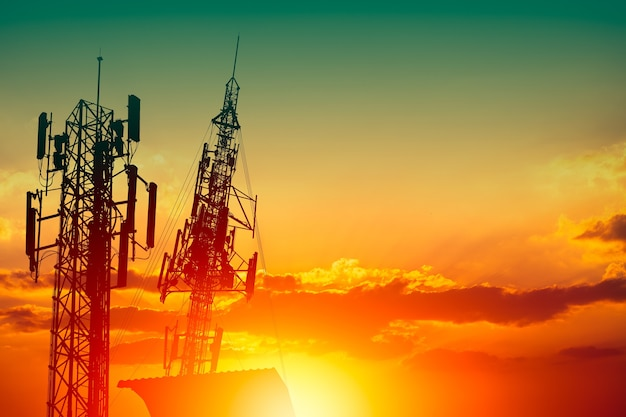 Silhouette of high frequency 5g station communication tower or 4g network telephone cellsite with dusk sunset sky with space for text