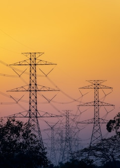 Silhouette of high-tension electric poles on sunset sky