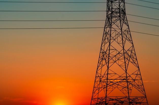 Силуэт высоковольтных электрических опор и электрических проводов с оранжевым небом