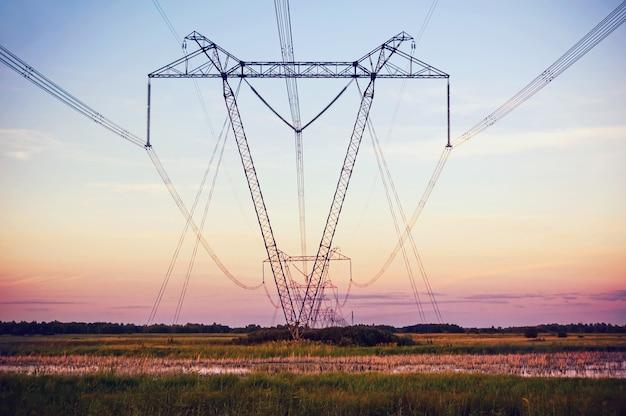 Силуэт высоковольтная электрическая башня на время заката и небо на фоне времени заката.