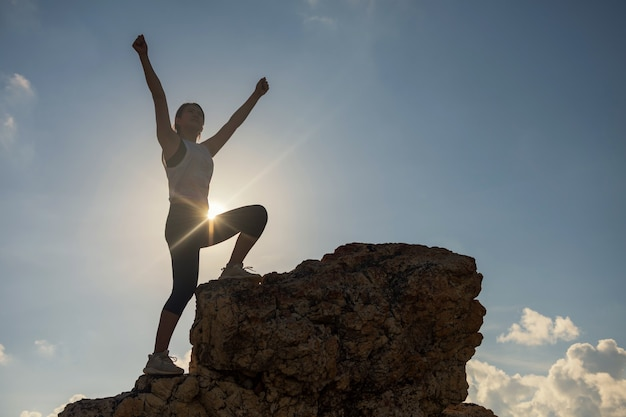 Silhouette hiking woman raise hands on top of hill during sunset