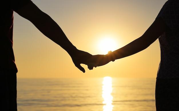 Силуэт, держась за руки против заходящего солнца