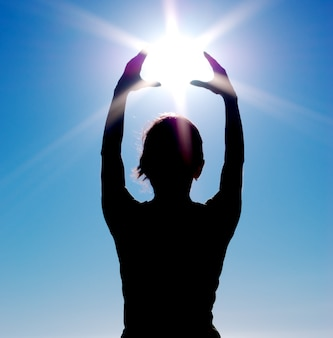 Silhouette holding the sun