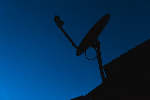 Silhouette home satellite dish digital tv antennas on the house roof on dark blue sky background