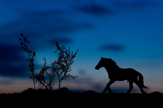 Silhouette of horse toy at sunset background.