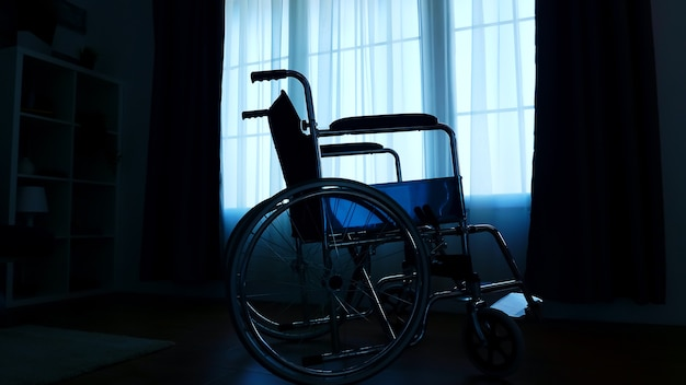 Silhouette of hospital wheelchair in dark room for people with mobility handicap.