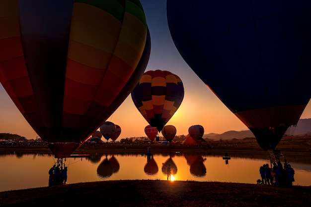 Silhouette hot air balloon over mountains lake landscape at sunset