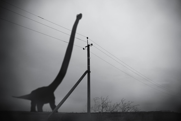 Silhouette of huge brontosaurus in dark fog and pillar with electric wires, gloomy fantastic collage