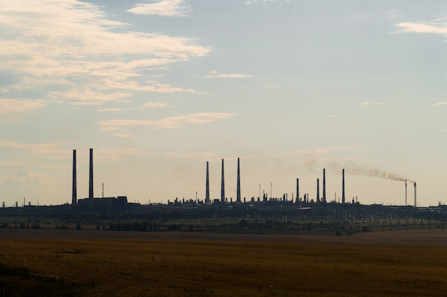 The silhouette of a huge gas and oil processing plant with burning torches, pipes and distillation of the complex.