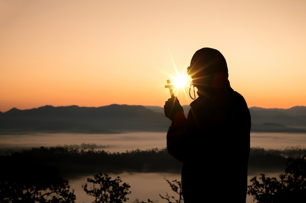 Silhouette of human hand holding the cross, the background is the sunrise.