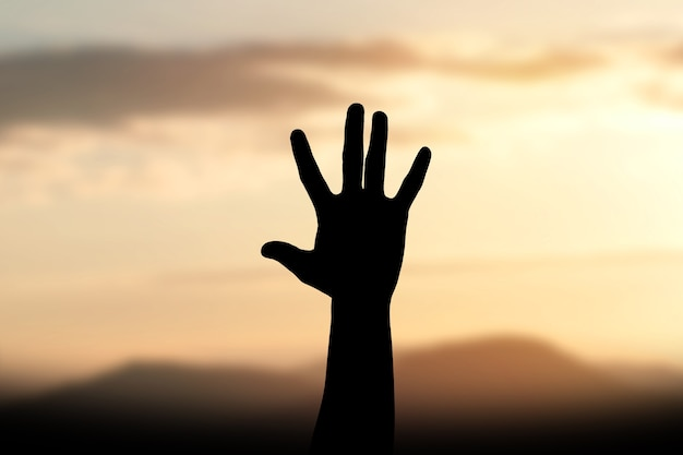 Silhouette human hands open palm up worship background