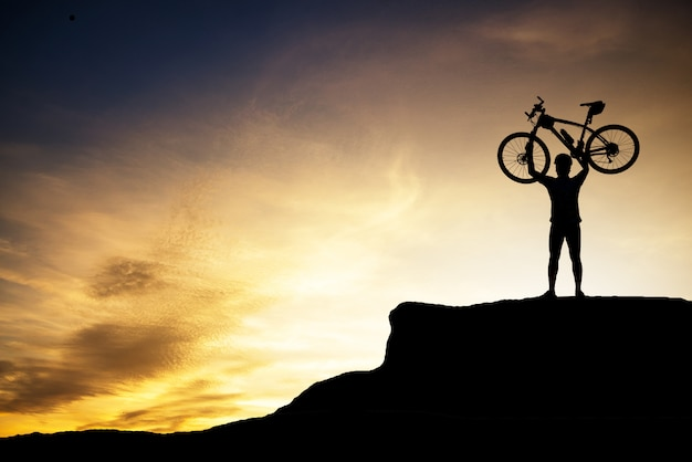 Silhouette of human holding mountain bike