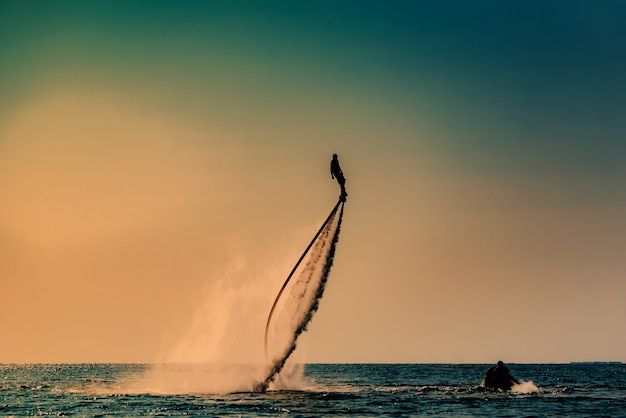 Silhouette image of a man showing the fly board (aqua board) at sea