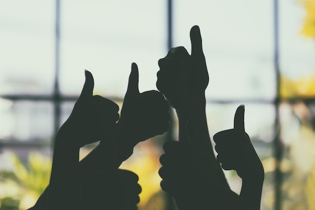 Silhouette image of many people's hands making thumb up sign