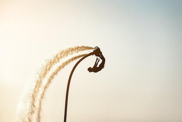 Silhouette изображение человека показывая доску мухы (доска aqua) на море; новый зрелищный экстремальный спорт