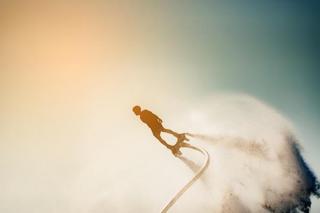 Силуэт изображение человека, показывая летать доска (аква-доска) в море