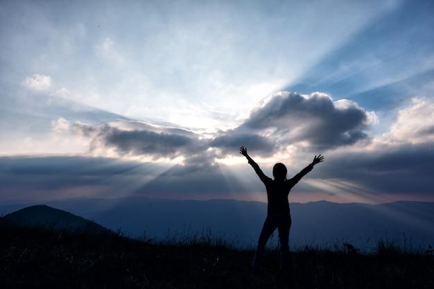 立って手を上げて、夕方に山の景色と夕日を見ている女性のシルエット画像