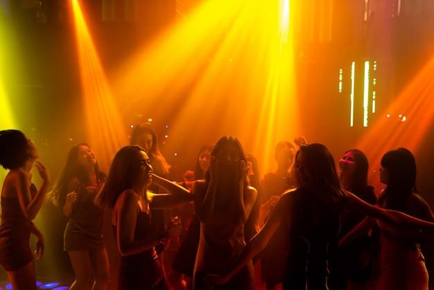 Силуэт изображения людей танцуют в ночном клубе диско под музыку от ди-джея на сцене
