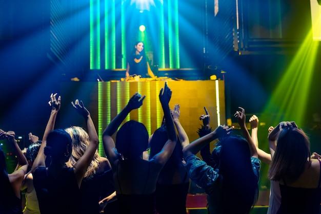 디스코 나이트 클럽에서 무대에서 dj의 음악에 맞춰 춤을 추는 사람들의 실루엣 이미지