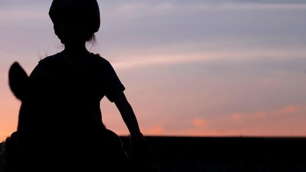 馬に乗っている小学生の女の子のシルエット画像は、夕暮れの空に逆らいます。