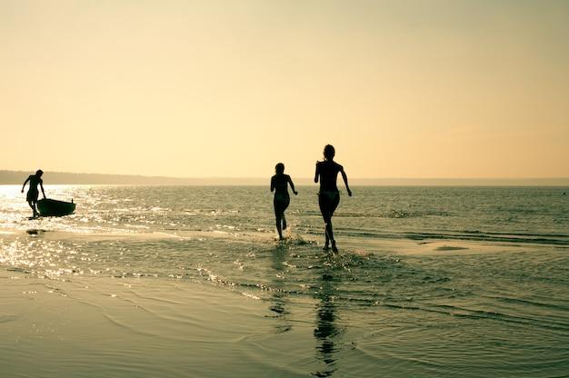 Силуэт изображения двух бегущих девушек и мускулистого мужчины в воде
