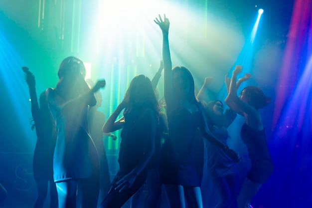 Silhouette image of people dance in disco night club to music from dj on stage