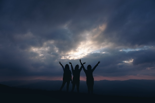 Silhouette image of three women standing and raising hands, watching sunset with mountains view in the evening