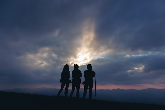 Silhouette image of three women standing and watching sunset with mountains view in the evening