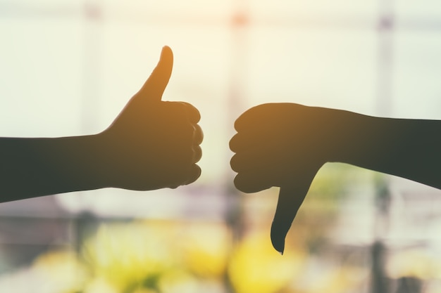 Silhouette image of two hands making thumbs up and thumbs down sign