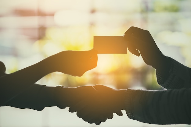 Silhouette image of two people shaking hands and exchanging empty business card