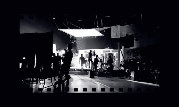 촬영 팀의 라이트 맨과 스튜디오에서 영화 감독과 함께 작업하는 비디오 카메라맨을 촬영하는 장면이나 비롤 또는 tv 광고 영화 제작 뒤의 비디오 제작 실루엣 이미지.