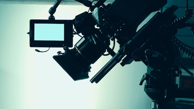 Silhouette images of video camera in tv commercial studio production which operating or shooting by cameraman and film crew team in set and prop on professional crane and tripod for easy to use