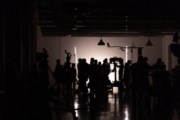 Silhouette images of video production behind the scenes, team lightman and cameraman working together with the director in the studio