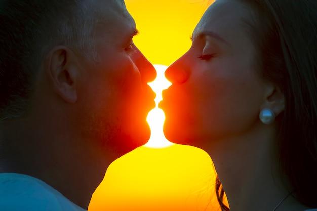 석양을 배경으로 한 남자와 여자의 얼굴의 실루엣. 사랑하는 부부의 관계에서 사랑과 로맨스