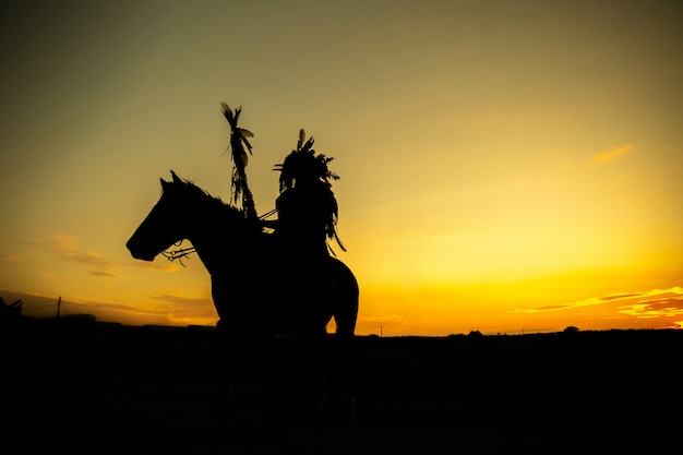 Silhouette of an indian man on a horse at sunset