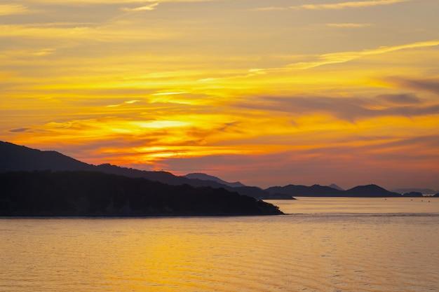 カラフルな明るい背景に夕日とシルエット島