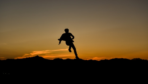 Silhouette of a jumping man at sunset