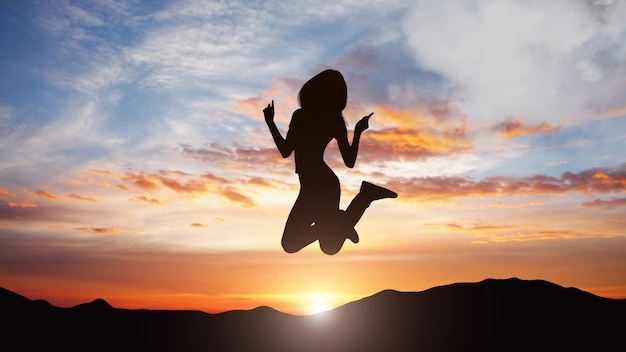 Silhouette of jumping woman against sunset background