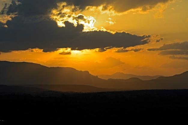 アフリカのサバンナの日没時のシルエットケニアの山々。ケニア