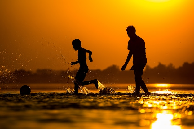 Silhouette of kids playing football on the beach