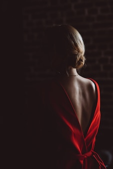 Silhouette of lady girl in red lodge with an open back in dark room.  beauty and fashion.