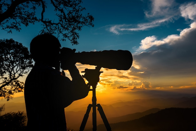 Silhouette of a landscape photographer use super telephoto lens at top of mountains during the sunset with two tone sunset sky