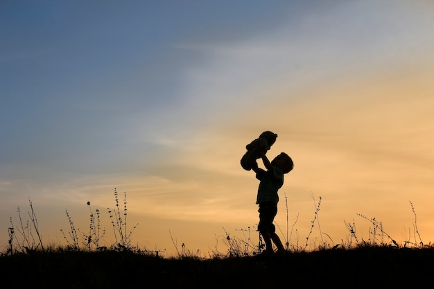 Silhouette of little boy with bear on sunset