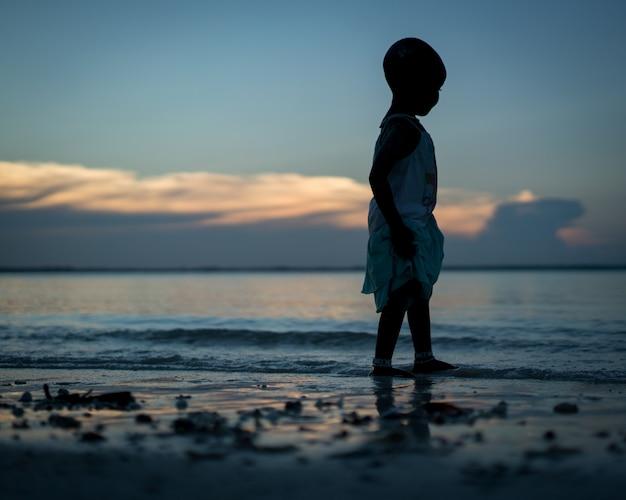 Silhouette of little girl on beach