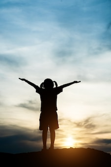 Silhouette of little girl raising hand to freedom happy time