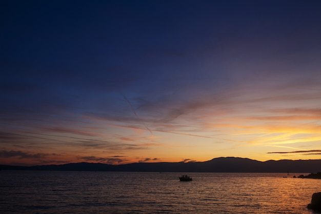 Silhouette of lonely boat in the sunset with dramatic sky. high seas sunset with a fishing ship on the horizon.