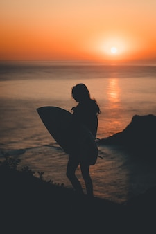 Silhouette of a lonely female holding a surfing board walking by the sea at sunset
